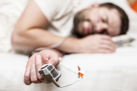 Man in bed - home sleep apnea study.