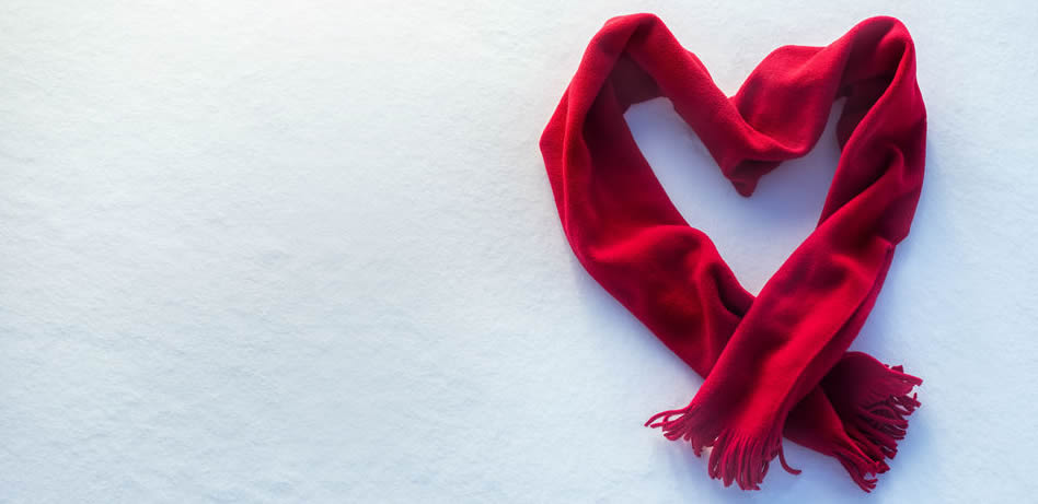 A red scarf in the shape of a heart on the snow.