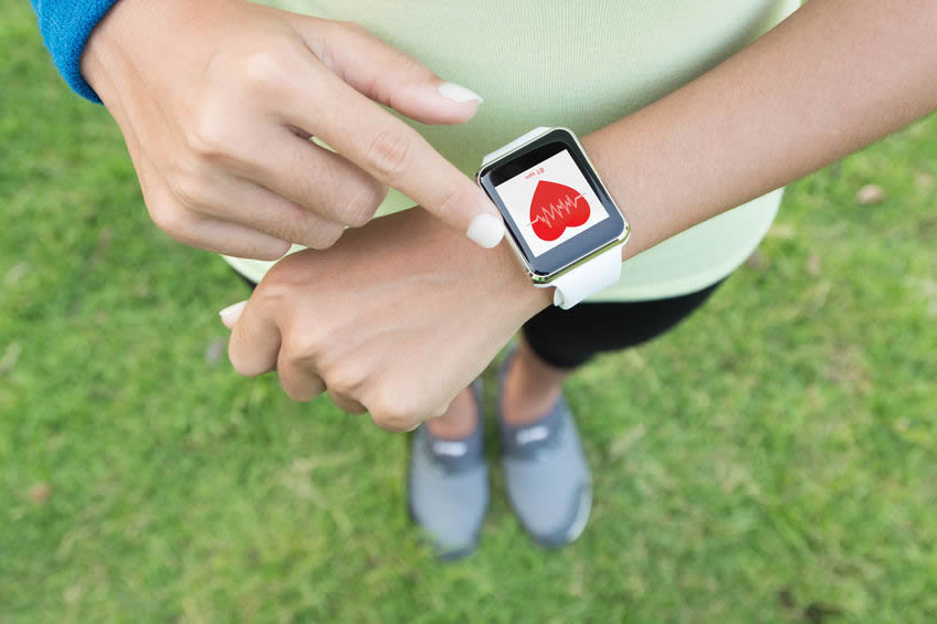 Woman checking heart rate on smart watch after exercising.