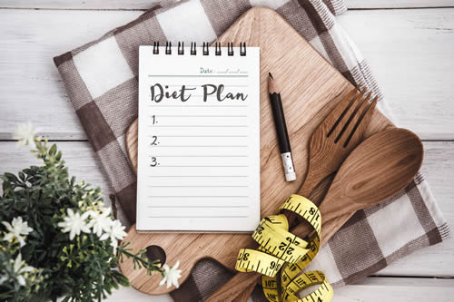 Notepad with Diet Plan list text on chopping board.