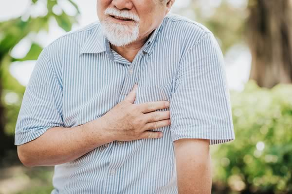 Senior man holding his chest and feeling pain suffering from heart attack.